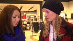 Young beautiful girls in a clothing store shopping - admire their clothes - stock footage