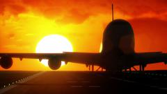Jet plane departs from airport runway as silhouette in front of large sunset Stock Footage