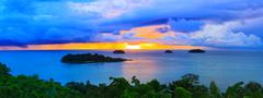 Panorama scene of raining clouds and sun set sky behind koh chang island in t Stock Photos