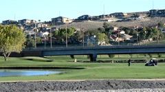 Golfers on course near houses and a highway 1 Stock Footage