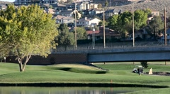 Golfers on course near houses and a highway 2 Stock Footage
