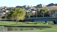 Golfers on course near houses and a highway 3 Stock Footage