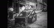 Civil defence worker cleaning debris from road with bulldozer Stock Footage