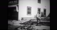 Volunteer spraying insecticides over debris outside shop Stock Footage
