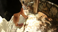 Woman rinsing sand off feet and sandals shoes Stock Footage