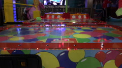 Mother with her baby having fun in the children's play air hockey Stock Footage