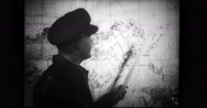 Military officer pointing at the map while briefing the soldiers Stock Footage