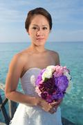asian beautiful bride holding her flowers - stock photo
