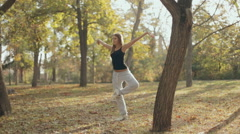 Girl retains a sense of balance and equilibrium in the park Stock Footage