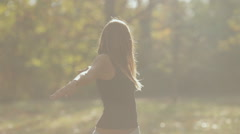 Calm girl with headphones make sudden movements by hands on the nature Stock Footage