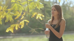 Beautiful girl in the park opens and drinks pure water from a bottle Stock Footage