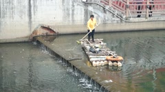 Female sanitation workers clean up garbage in the river, in Shenzhen, China - stock footage