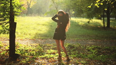 Young girl turned towards the sun in the autumn park Stock Footage