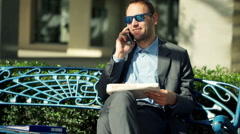 Handsome businessman calling for job in a response to a newspaper ad  HD Stock Footage