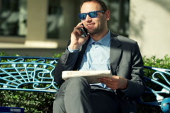 Handsome businessman calling for job in a response to a newspaper ad  NTSC Stock Footage