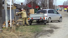 Peasant unloads firewood for the stove in the Russian village. Stock Footage
