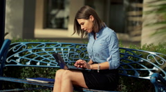 Businesswoman finishing work on laptop and relaxing at the city bench HD Stock Footage