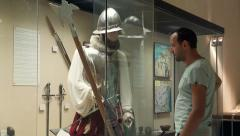 Young, handsome man enjoying a museum exhibit of military uniforms HD Stock Footage