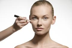 Stock Photo of natural woman applying cosmetics on her visage