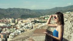 Beautiful woman looking at ancient ruins and amazing cityscape  HD Stock Footage