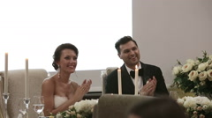 Newlyweds at the wedding sitting at the table for a festive applauded and smile Stock Footage