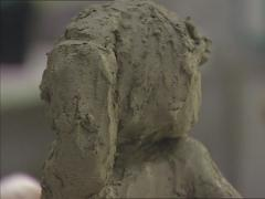 Artist modelling a clay bust using a wire end tool Stock Footage