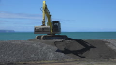 Excavator working on shingle bank seawall HD - stock footage