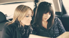 Two Women Reading Map in the car - stock footage