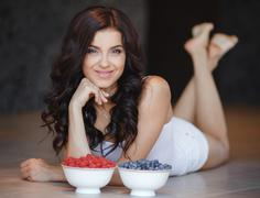 Portrait of beautiful young woman eating a bowl of blueberries and smiling. - stock photo