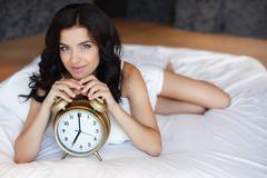 Young woman with alarmclock on the bed at the morning. - stock photo