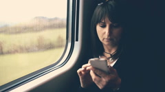 Woman using smartphone in train. Handheld shot Stock Footage
