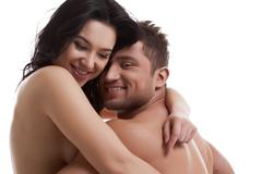 Smiling nude lovers hugging at camera - stock photo