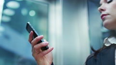 Business Woman in Dark Suit using Mobile Phone in Elevator. Stock Footage