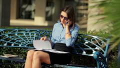 Businesswoman talking on cellphone and reading documents sitting on bench HD Stock Footage
