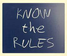 """""""Know the rules"""" handwritten with white chalk on a blackboard Stock Photos"""