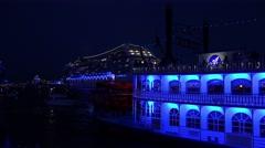 4k Blue illuminated paddle steamer and cruise ship cruising night Stock Footage