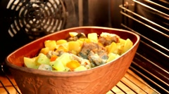 Ceramic sauce pot with stew meat in oven Stock Footage