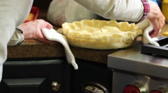 Putting the apple pie crust in oven Stock Footage