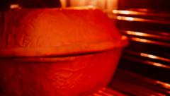 Ceramic sauce pot with cover in the oven. Stock Footage