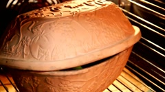 Ceramic sauce pot  with cover  in the oven Stock Footage