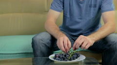 Eating grapes on living room table - stock footage