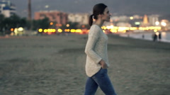 Pretty woman looking around standing on beach in the evening HD Stock Footage