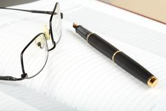 business a still-life with fountain pen and glasses - stock photo