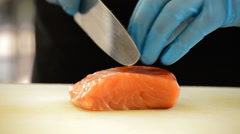 Professional chef hands cutting a salmon fillet Stock Footage