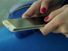 Close up of woman hands texting, sending sms on smartphone in city NTSC Stock Footage