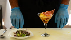 Hands of professional chef decorating cup mango fruit and ham with herbs Stock Footage