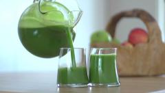 Pouring green juice into glass - stock footage