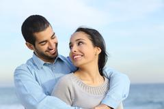 Arab casual couple cuddling happy with love on the beach - stock photo