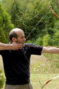 Man shooting with bow Stock Photos