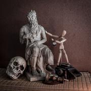 still life of moses statue ,skull,wooden figure on mat - stock photo